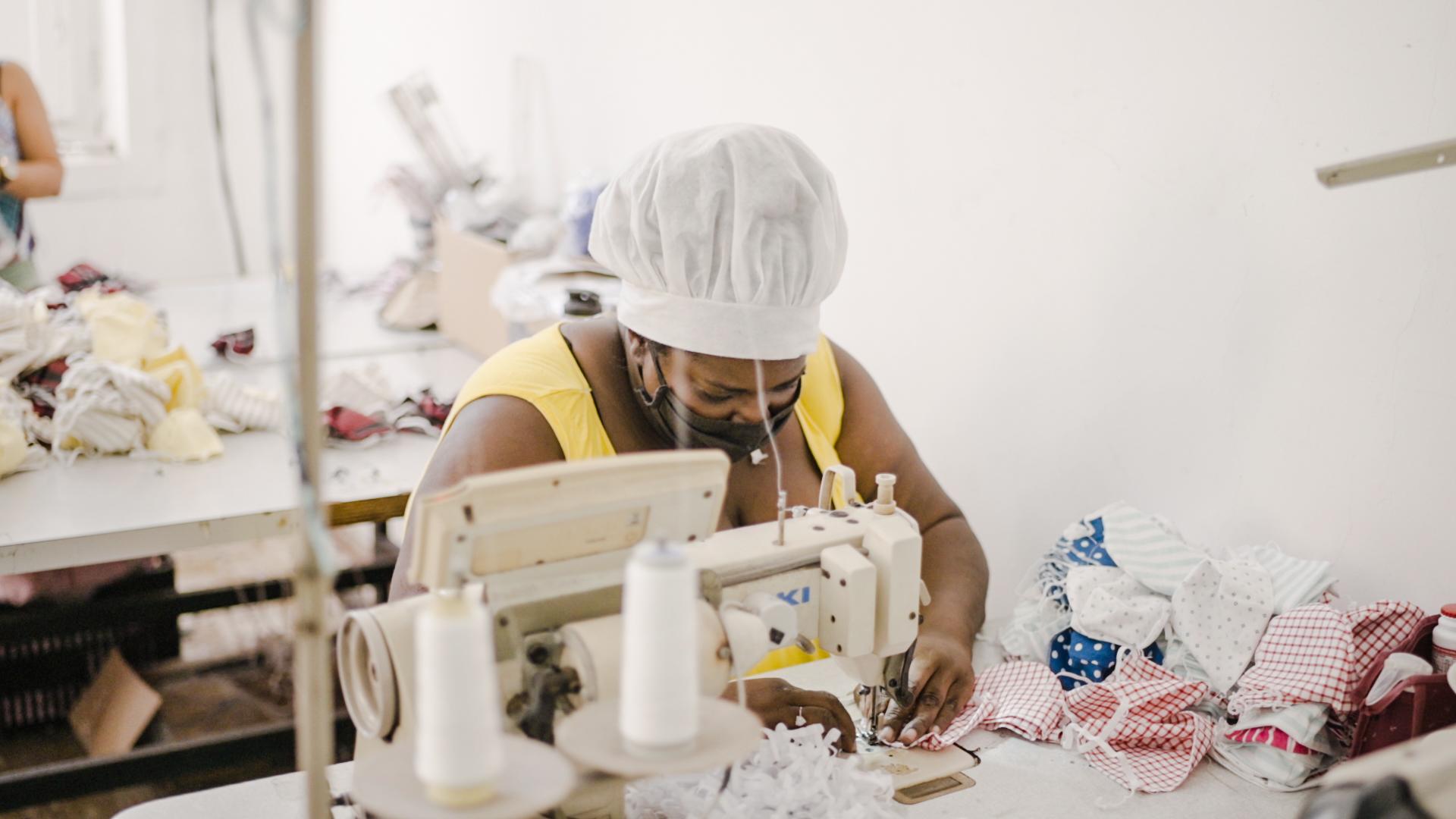 Senhora participante do Rede + Renda usando a máquina de costura.
