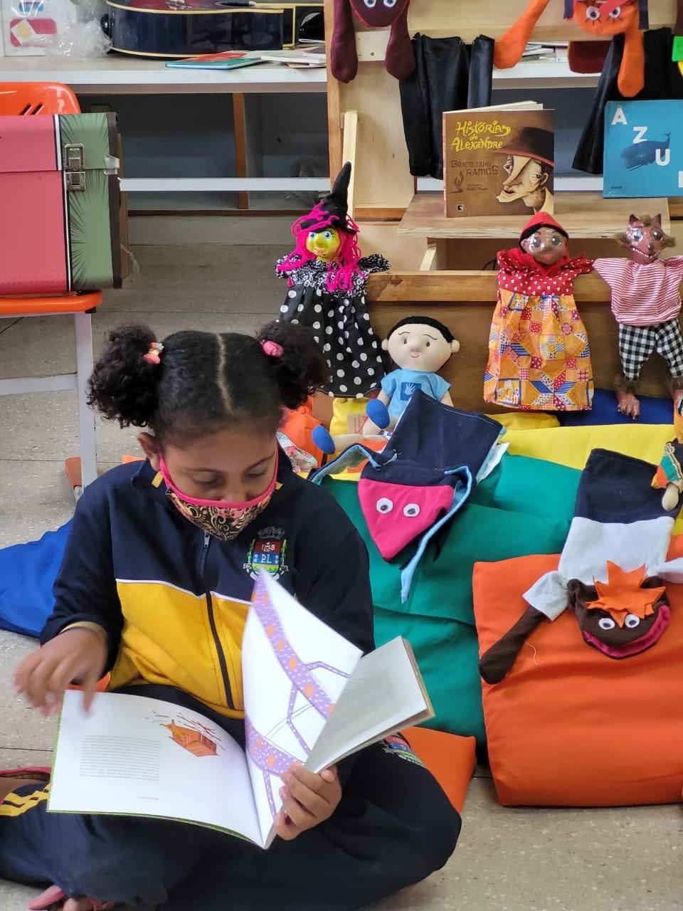 Menina sentada no chão da escola entre as almofadas, lendo o livro que segura com suas mãos e apoia em seu colo.