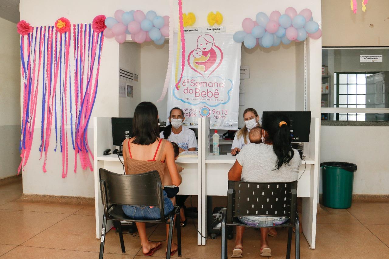 """Imagem de quatro mulheres sentadas nas suas respectivas cadeiras: duas mães segurando as crianças no colo de frente a outras duas mulheres com a camisa do evento """"Semana do bebê""""."""